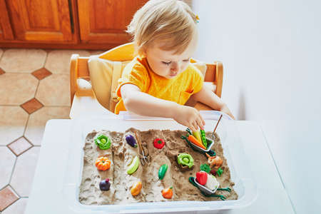 Adorable little girl playing with toy fruits and vegetables and kinetic sand at home, in kindergaten or preschool. Indoor creative games for kids Stock fotó