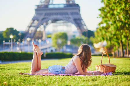 Beautiful young girl having picnic near the Eiffel tower in Paris. Tourist enjoying her vacation in France