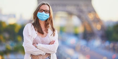 Girl standing near the Eiffel tower in Paris and wearing protective face mask. Tourist spending vacation in France during pandemic