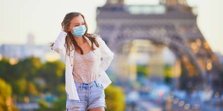 Young girl standing near the Eiffel tower in Paris and wearing protective face mask during coronavirus outbreak. Pandemic and lockdown in France. Tourist spending vacation in France after quarantine