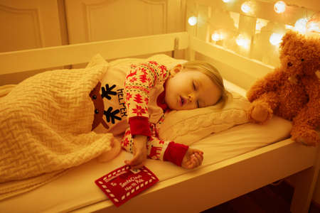 Adorable toddler girl sleeping with teddy bear and letter to Santa Claus in her hand under the Christmas tree. Child dreaming in bed on New Year eve.