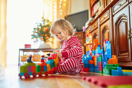 Adorable toddler girl in pajamas playing with presents on Christmas morning. Celebrating seasonal holidays with kids Stock Photo