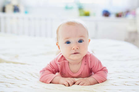 Adorable baby girl lying on bed on her tummy. Happy healthy little child practice crawling. Infant kid in sunny nursery doing tummy time