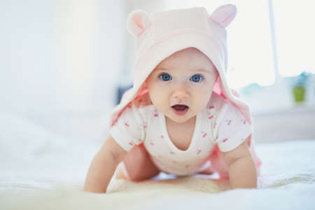 Adorable seven months baby girl relaxing in bedroom in pink clothes or towel with ears Foto de archivo