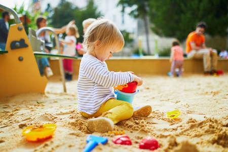 可爱的小女孩在操场上的沙坑。蹒跚学步的孩子玩沙模,做泥饼。儿童户外创意活动
