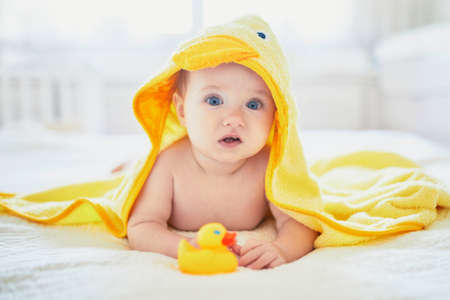 Cute little girl playing with rubber duck after having bath. Happy kid in yellow towel