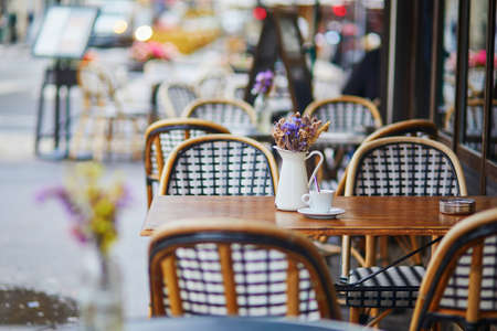 Table of traditional Parisian outdoor cafe. Cup of coffee and pitcher with dried flowers in empty restaurant in Paris, France