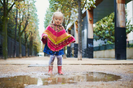Child wearing red rain boots and jumping in puddle on a fall day. Adorable toddler girl having fun with water and mud in park on a rainy day. Outdoor autumn activities for kids