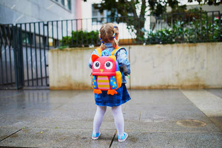 Adorable toddler girl with funny backpack ready to go to daycare, kindergarten or school. First day of school concept