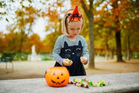 Adorable toddler girl in black cat dress with tutu skirt trick-or-treating with orange pumpkin bucket. Happy kid celebrating Halloween in Paris, France
