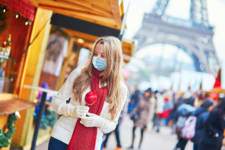 Girl wearing face mask with caramel apple on Parisian Christmas market near white snowy Christmas tree with Eiffel tower in the background. Seasonal holidays during pandemic and coronavirus outbreak