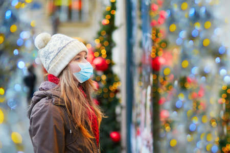 Girl wearing face mask on a Parisian street or at Christmas market looking at shop windows decorated for Christmas. Seasonal holidays during pandemic and coronavirus outbreak Stock Photo