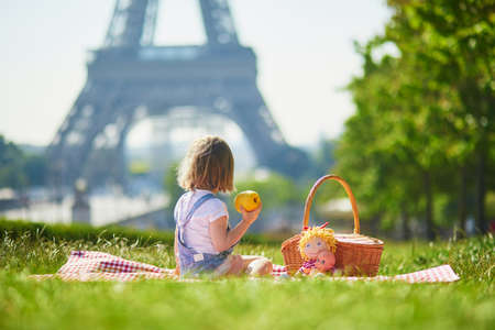 Cheerful toddler girl having picnic near the Eiffel tower in Paris, France. Happy child playing with toys in park on a summer day. Kid enjoying healthy snacks outdoors Banque d'images