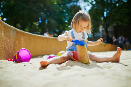 Adorable little girl having fun on playground in sandpit. Toddler playing with sand. Outdoor creative activities for kids