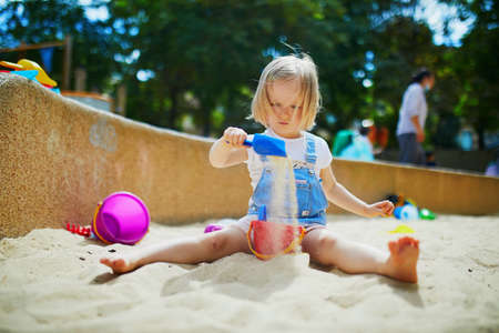 Adorable little girl having fun on playground in sandpit. Toddler playing with sand. Outdoor creative activities for kids Stock Photo