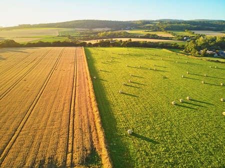 Aerial view of pastures and farmlands in Brittany, France. Beautiful French countryside with green fields and meadows. Rural landscape on sunset Stock Photo