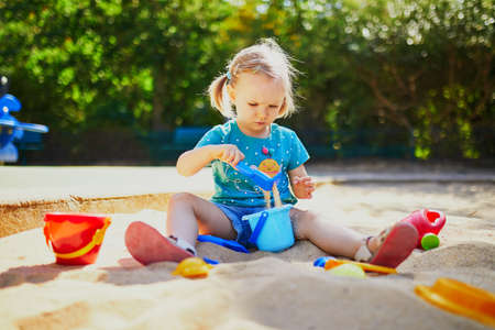 Adorable little girl having fun on playground in sandpit. Toddler playing with sand molds and making mudpies. Outdoor creative activities for kids Zdjęcie Seryjne