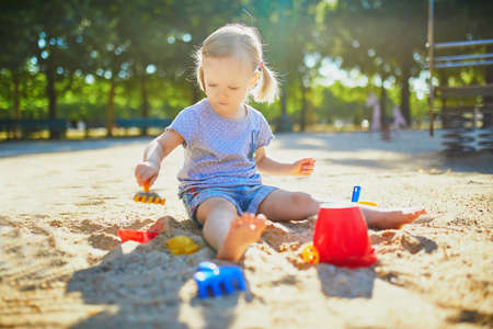 Adorable little girl having fun on playground in sandpit. Toddler playing with sand molds and making mudpies. Outdoor creative activities for kids