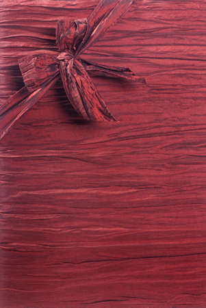 Vertical crimson red fabric textured gift background with a ribbon and box in the upper left corner running diagonally. 版權商用圖片