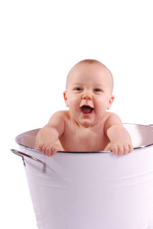 Vertical image of a cute, laughing baby in a white tub against a white background.