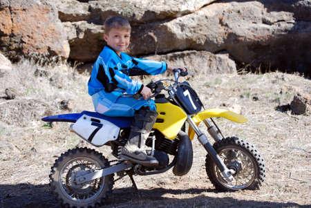 motorcross: Horizontal de la imagen de un joven atleta masculino parque sentado en su moto en el desierto, en contra de un afloramiento volc�nico de rimrock.