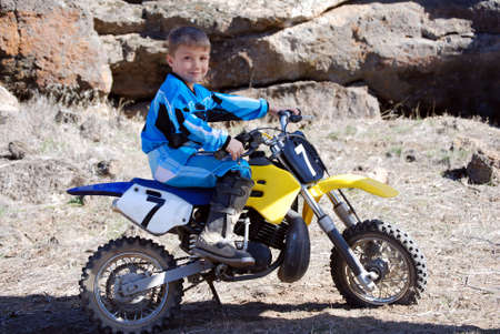 Horizontal image of a young male motorcross racer sitting on his motorbike in the desert, against an outcrop of volcanic rimrock.