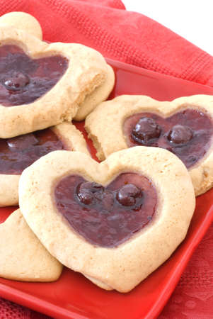 Heart shaped cherry filled cookies on a red plate. Stock Photo