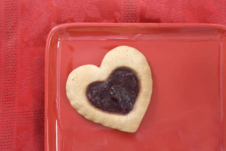 Cherry filled heart cookie on a red plate against a red tablecloth