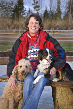 Vertical image of a woman sitting outdoors with her Standard Poodle and Miniature Australian Shepherd. Focus on womans face.