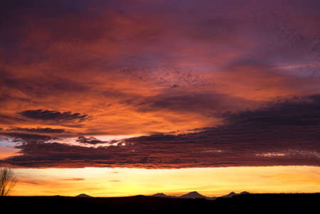 Horizontal image of a colorful warm sunset over the Cascade Mountains in Central Oregon.