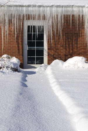 ice dam: Glass door in a red brick wall nearly occluded by long sharp icicles.  Path to the doorway is covered in snow.