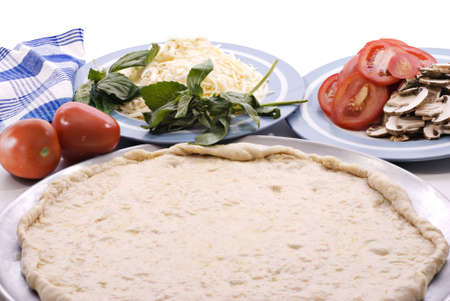 Ongekookt pizza deeg, Roma tomaten, basilicum, gesneden champignons en mozzarella kaas klaar om te monteren.