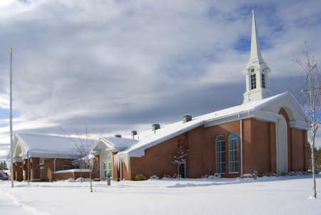 A red brick church covered in snow, standing in a snowy field with its steeple against a blue break in the cloudy sky.