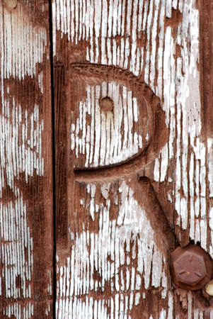 Image of a western branding iron brand burned into a vintage wooden door with old peeling paint and a rusty bolt.