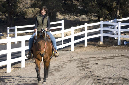 A dark haired attractive woman riding a beautiful bay quarter horse wester/natural horsemanship style in a white fenced arena. 写真素材