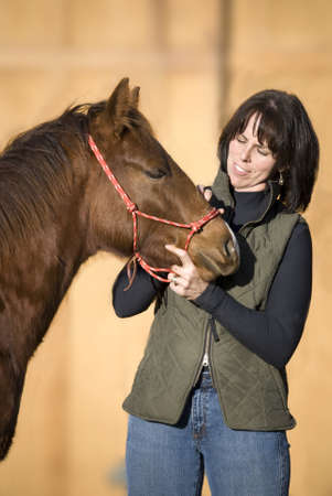 Pretty dark haired woman standing with her sorrel (chestnut) quarter horse foal against an out of focus barn. Stock Photo