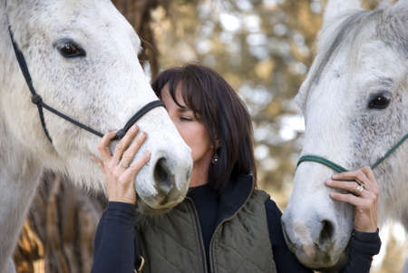 A pretty dark haired woman with two grey horses is kissing one of them on the muzzle. Stock Photo