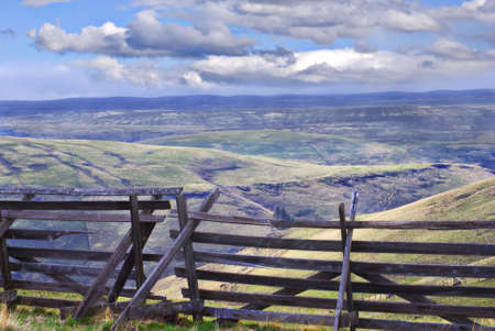 Horizontal landscape of eastern Oregon south of Pilot Rock with an old wooden snow fence in the foreground and blue cloudy skies in the background. Stock Photo