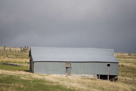Gray galvanized metal farm building against brooding grey skies in eastern Oregon.  (South of Pilot Rock between mm 34B and 35B on hwy 395) Banco de Imagens