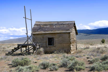 Abandoned, derelict old west jail and gallows out on the alkali plains.