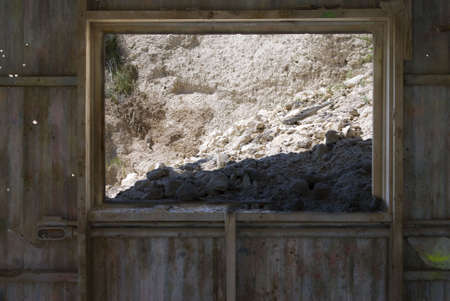 Mined diatomaceous Earth falling through the window of an old abandoned mine.