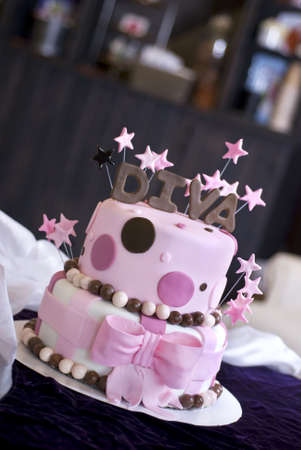 A pink fondant cake with Diva and stars topping it featured in a bakery.  Shallow DOF with focus on the front of the cake.