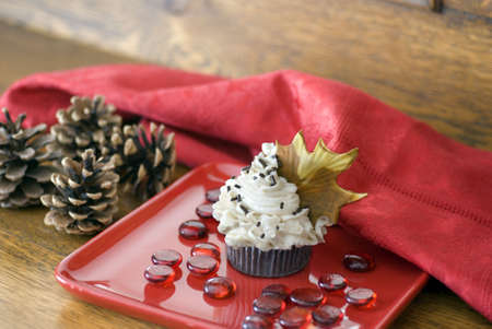An autumn themed chocolate cupcake with a brown fondant maple leaf garnish on a red dessert plate.