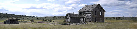 Panoramic view of back of 19th century homestead house with horse barn and windmill.  Measures 55.296