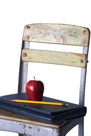 255 흰색 배경에 대해 좌석에 빨간 사과와 날카로운 연필로 폐쇄 된 노트북을 들고는 오래 된 학교의 자.
