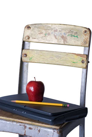 An old school chair holding a closed laptop with a red apple and sharp pencil on the seat, against a 255 white background.