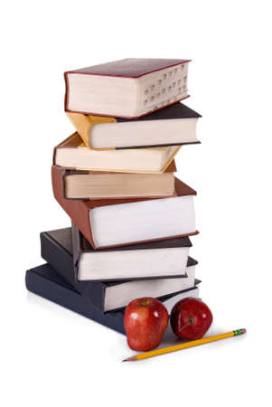 A vertical stack of hardbound books with two apples and a pencil in the foreground against a white background.