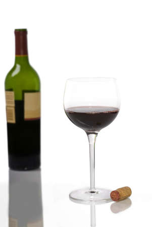 A glass of red wine in the foreground with a cork beside it and an out of focus bottle of red wine in the background, all with reflections.   Stock Photo