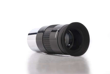 eyepiece: Close-up image of a black and metallic telescope eyepiece on a white background with a mild relfectionshadow beneath. Stock Photo