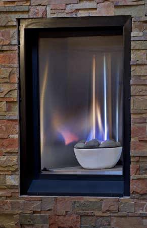 chemin�e gaz: Un foyer � gaz confortable avec des flammes bleues et jaune serti dans un cadre chaleureux mur, dalle